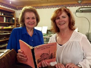 Program committee chairwoman Linda (Cinson) Faa is pictured here (left) looking over a vintage Malvern cookbook brought in by society follower Lorraine (Galay) Baldwin.